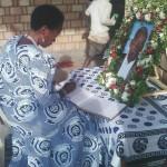 Prof Tibaijuka akisaini kitabu cha maombolezo katika msiba wa Ta Nshala
